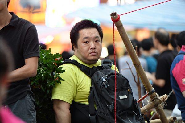 """2014年10月4日,中共控制的黑帮成员与外围组织以""""反占中""""的名义,在旺角的""""雨伞运动""""和平集会地点挑衅,想引起骚乱,制造清场的借口。图为""""香港人优先""""发起人张汉贤(Dickson)。他曾被安排于去年12月炮制轰动国际的""""闯军营""""事件、今年9月又冒充法轮功,这次出现在旺角学生和平集会上。(宋祥龙/大纪元)"""