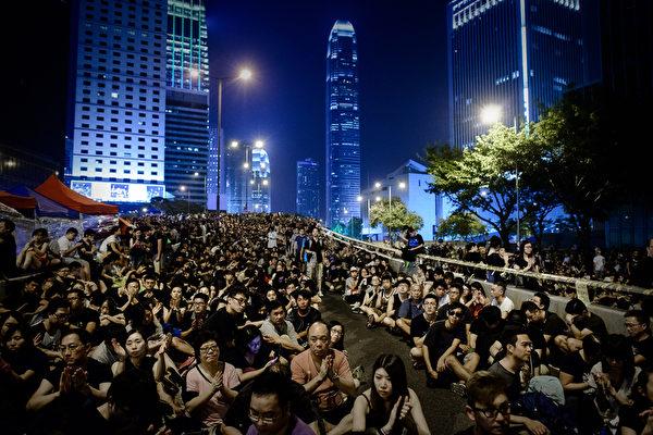 """2014年10月4日,""""全民反暴、和平抗争""""活动在金钟进行,民众同时打开手机灯光,照亮香港夜空。(Philippe Lopez/AFP)"""