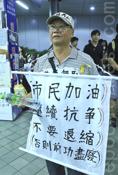 """""""全民反暴、和平抗争""""活动,10月4日晚间在金钟的香港政府总部前进行,有市民带来标语支持学生坚持留守到最后一刻。(余钢/大纪元)"""
