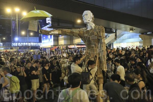 2014年10月5日晚,傳警方將會武力清場,部分學生、市民在政府總部外面留守,學生豎立象徵雨傘運動的巨人。(余鋼/大紀元)