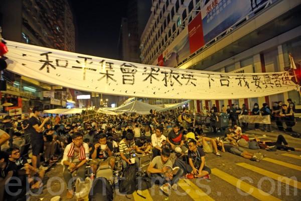 香港雨伞运动10月5日步入第七天,在暴力袭击下,各界纷纷呼吁学生撤离占领地,不过学联决定继续坚持,在黑社会恐吓最严重的旺角占领区,许多市民纷纷响应,通宵留守。(潘在殊/大纪元)