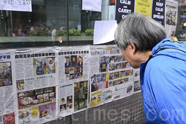 《大紀元時報》在香港雨傘運動期間,詳實、客觀的報導備受市民歡迎。圖為2014年10月6日,香港街頭不少市民駐足觀看張貼的大紀元時報。(余鋼/大紀元)