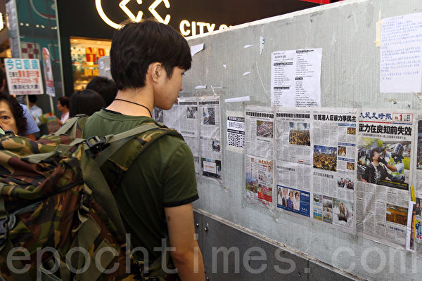 《大紀元時報》在香港雨傘運動期間,詳實、客觀的報導備受市民歡迎。圖為2014年10月6日,在旺角佔領區集會,不少市民駐足觀看張貼的大紀元時報。(潘在殊/大紀元)