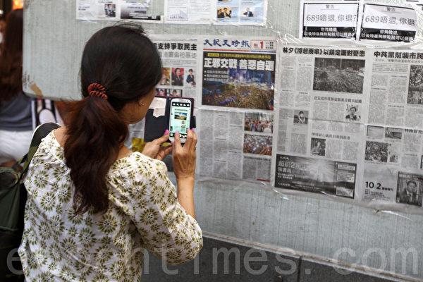 香港雨傘運動10月6日進入第九日,仍然有大批市民無懼黑社會的恐嚇,在旺角佔領區集會,不少市民駐足觀看張貼的大紀元時報。(潘在殊/大紀元)