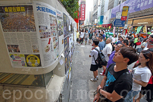 《大紀元時報》的記者團隊,在香港雨傘運動期間,詳實、客觀的報導備受市民歡迎。圖為2014年10月6日,在旺角佔領區集會,不少市民駐足觀看張貼的大紀元時報。(潘在殊/大紀元)