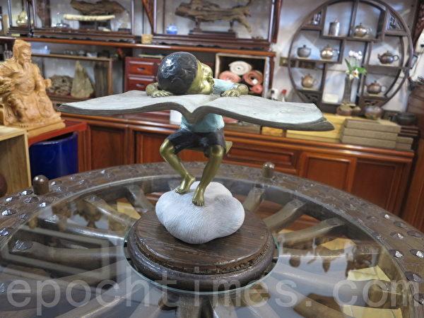 木雕街展示的铜雕艺术--忘情书海,作者陈绍宏。(赖瑞/大纪元)