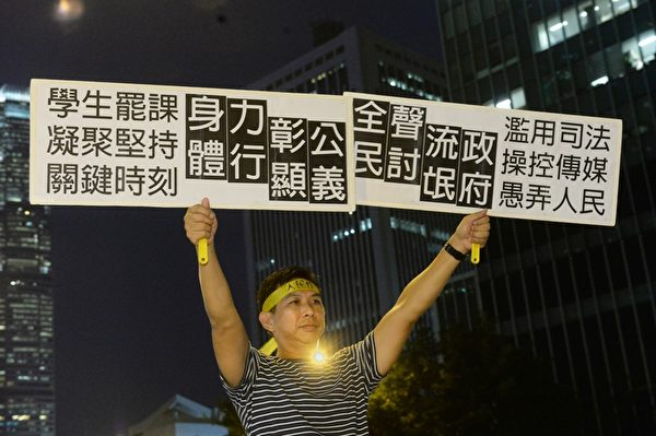 2014年10月7日,雨伞运动进入第10日。金钟现场平静,现场有市民高举自制的展示牌,表达诉求。(宋祥龙/大纪元)