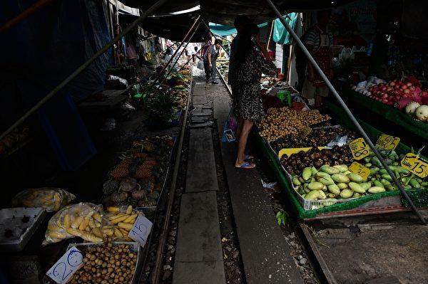 火车驶过之处,菜贩从新支起布篷,继续招呼顾客。(CHRISTOPHE ARCHAMBAULT/AFP/Getty Images)