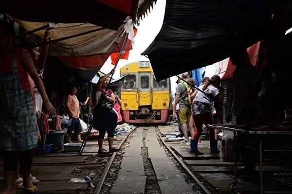 火车驶来,菜贩们准备收起布篷。(CHRISTOPHE ARCHAMBAULT/AFP/Getty Images)