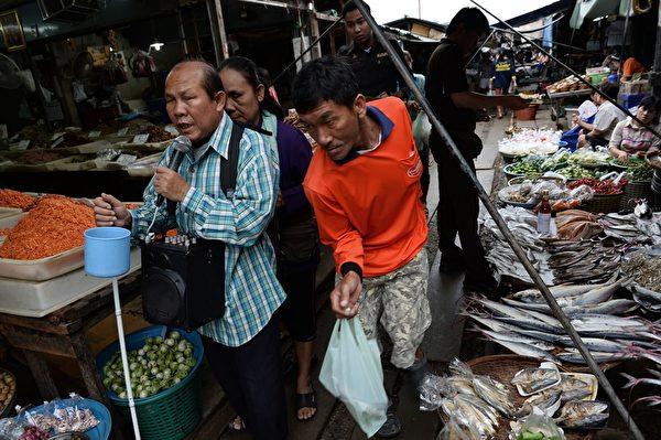 美功菜市场,走在铁轨上的顾客和行乞的盲人。(CHRISTOPHE ARCHAMBAULT/AFP/Getty Images)