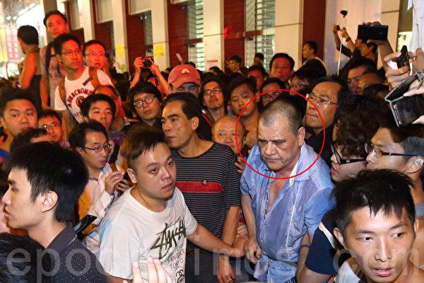 """2014年10月3日,香港大批支持""""雨伞运动""""的市民无惧黑社会的暴力恐吓,包围旺角现场的黑社会组织""""和胜和""""小头目大鬼(红圈者),要求警方严正执法。(潘在殊/大纪元)"""