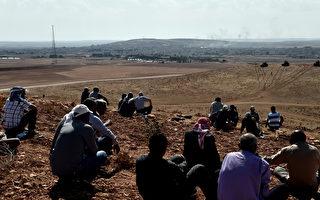 2014年10月9日,库尔德男士从土耳其桑尼乌法省东南部的土耳其村庄Mursitpinar边境山上,观看同胞与IS在叙利亚边城科巴尼的战斗。(AFP/ARIS MESSINIS)