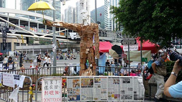 抗議現場的一尊大型雕像,手持象徵抗議活動的雨傘。在雕像的前方,《大紀元時報》如同海報般鋪滿鐵馬。(大紀元)