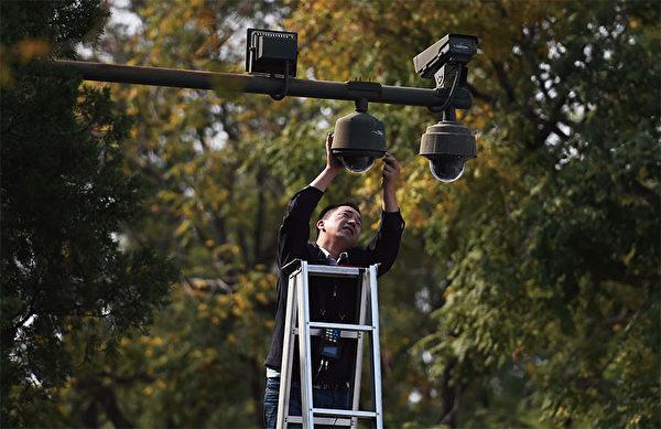 「十一」期間北京全面提升反恐、特警備勤等級。圖為9月30日,一名工人在調整監控北京天安門廣場的攝影鏡頭。(AFP)
