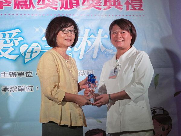 從事居家護理15年的護理師廖淑緣(右)接受縣長蘇治芬頒獎。(廖素貞/大紀元)
