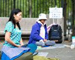 清晨,在纽约华埠苏域柏公园前,法轮功学员在祥和的音乐声中,打坐炼功。(Samira/大纪元)