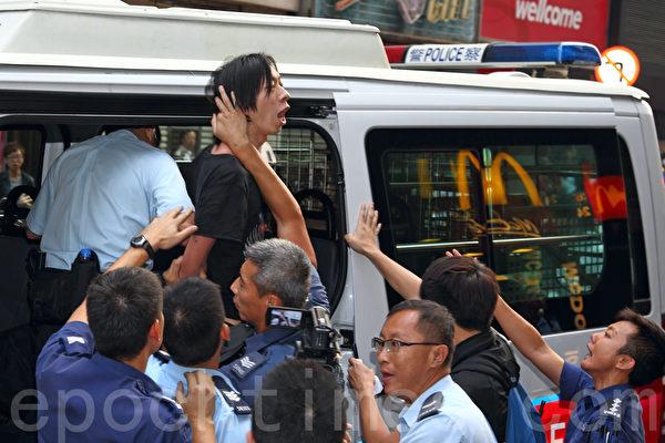 """香港""""雨伞运动""""进入第20日,警方10月17日凌晨五时左右突然出动大批警力进行清场。参与闯驻港部队军营的香港人优先成员招显聪被警察扣手铐制服带走。(潘在殊/大纪元)"""