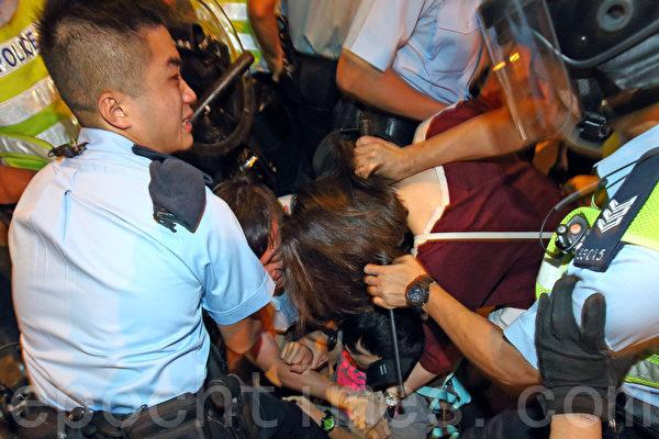 10月17日晚,旺角有9,000名香港民众和学生上街抗议,警察多次施放胡椒喷雾及挥动警棍试图驱散。图为男警员用警棍抵住女示威者的颈部往下摁,下面还有两位男士,做法粗暴。(潘在殊/大纪元)