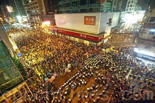 """9,000名香港民众和学生不满警方强行清场,10月17日晚上聚集在旺角""""雨伞运动""""集会区,与警方发生多次推撞。警察多次施放胡椒喷雾及挥动警棍试图驱散示威者,随着抗议人数不断增加,警方在凌晨12时左右被迫撤退,被大批市民包围。(潘在殊/大纪元)"""