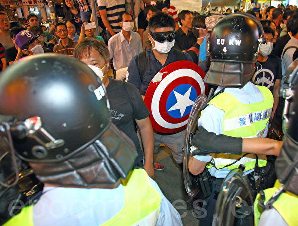 """9,000名香港民众和学生不满警方强行清场,10月17日晚上聚集在旺角""""雨伞运动""""集会区,与警方发生多次推撞。警察多次施放胡椒喷雾及挥动警棍试图驱散示威者。(潘在殊/大纪元)"""