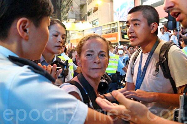 10月17日晚上8时许,曾夺得多个国际摄影奖项,获提名普立兹奖的美国女记者布龙斯坦(Paula Bronstein)(中)在香港旺角采访示威活动期间被警察拘捕,现场的多名同行试图劝阻警方采取行动。(蔡雯文/大纪元)