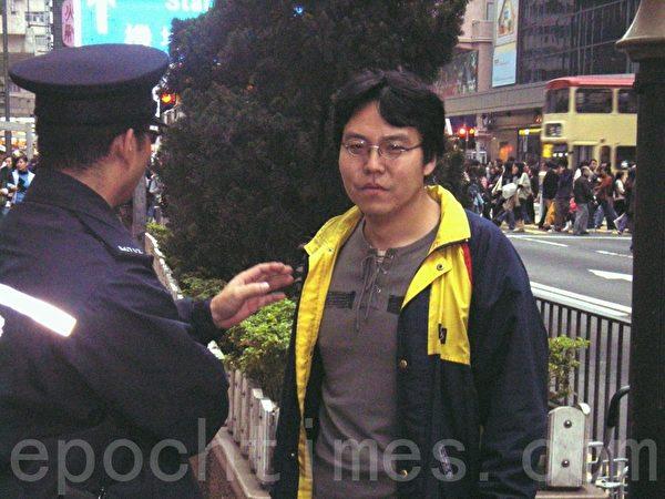 """一名多年来滋扰跟踪法轮功学员的男子,18日晚上在旺角弥敦道的防线前与市民口角,又喊起""""打倒共产党"""",身份诡异。大纪元早在2006年就曾拍下此人企图破坏旺角的法轮功真相点,被警方制止。(大纪元)"""