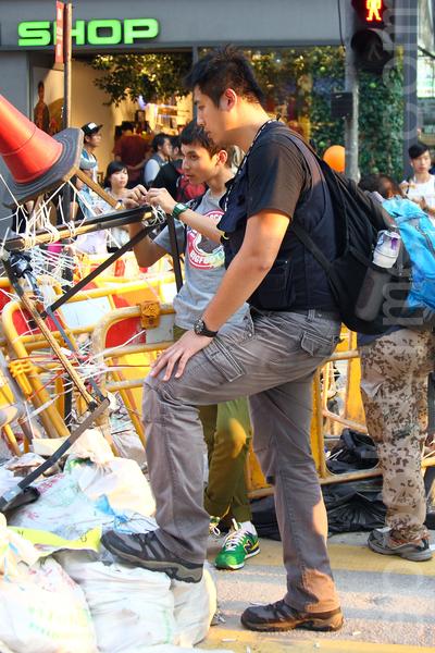 """曾假扮法轮功的""""香港人优先""""张汉贤其中一名手下,连日来混入""""雨伞运动""""的旺角集会区,打扮成""""美国队长""""多次带头冲击警方防线。(潘在殊/大纪元)"""