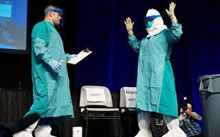 10月21日,纽约市上千名医保人员在贾维茨会展中心接受埃博拉培训和动员。图为培训中示范如何穿戴防护设备。(州长办公室提供)