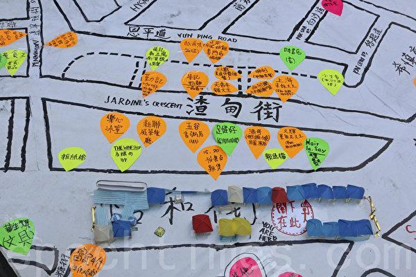 """10月22日,""""雨伞运动""""进入第25日,铜锣湾街头仍有学生市民留守,图为留守人士制图让市民去小店消费,希望帮助受影响的小商户。(余钢/大纪元)"""