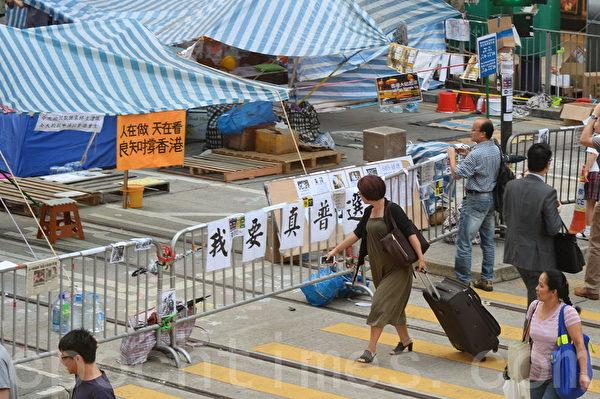"""""""雨伞运动""""铜锣湾集会区不但没有影响商家生意,还吸引许多大陆和各国游客成为拍照留念的新的观光景点。(宋祥龙/大纪元)"""