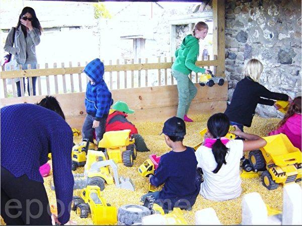 果园为孩子们准备的有玉米粒的小亭子,孩子们脱了鞋在里面尽情地玩玉米粒。(李文笛/大纪元)