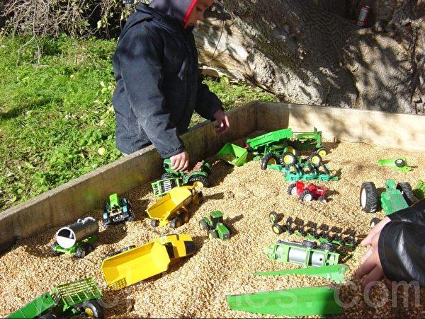 孩子们在用麦粒做的沙盘里玩玩具。(李文笛/大纪元)