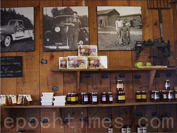 交易大厅里的商品——自制的蜂蜜,据说果园里有六个蜂房。墙上贴的老照片还有架子上的古董显示了果园的历史。(李文笛/大纪元)