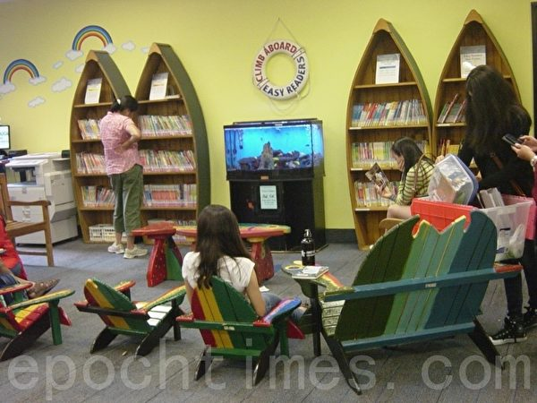市图书馆每天上午10~11时有老师教唱歌、玩游戏或讲故事,是孩子们很期盼的愉快时光。(李文笛/大纪元)