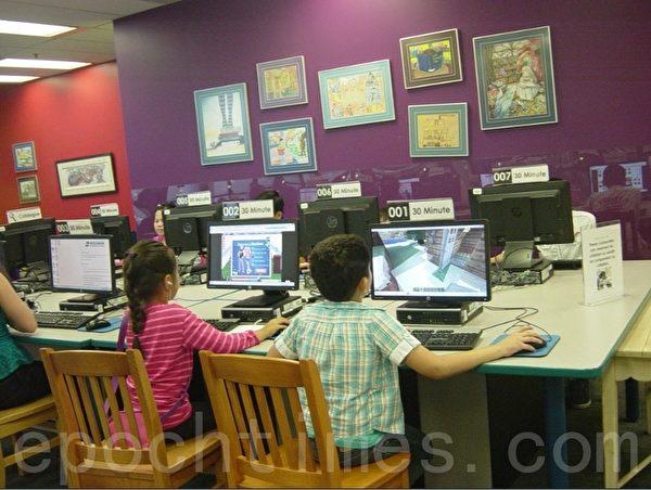 市图书馆的儿童阅览室里儿童在电脑上阅读,这里为儿童提供了许多电脑。(李文笛/大纪元)