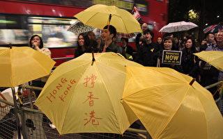 10月30日晚,近200位各界居英港人,包括來自大陸的華人,在香港財政司司長曾俊華,於倫敦梅菲爾出席香港貿易發展局週年晚宴的近四小時內,在會場外高舉雨傘、高呼口號表達支持香港真普選訴求。(曹鶯飛/大紀元)