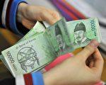 据彭博汇整的数据,韩元因美、日货币政策呈现分歧,支撑美元汇价,韩元汇率2014年11月3日,跌幅逾3年来连3日最大。(JUNG YEON-JE/AFP/Getty Images)