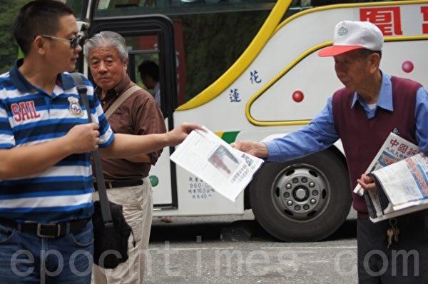 官老爹(右一)向游客发放法轮功真相资料。(詹亦菱/大纪元)