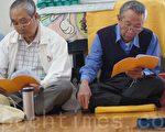 74岁的官老爹(右)修炼法轮功后无病一身轻,每天都做着自己应该做的,活得踏实、有意义。图为官老爹与其他法轮功学员一起集体阅读法轮功书籍。(詹亦菱/大纪元)