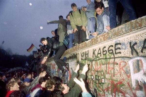 1989年12月22日,东德人在勃兰登堡门向西德柏林市民打招呼。(PATRICK HERTZOG/AFP/Getty Images)