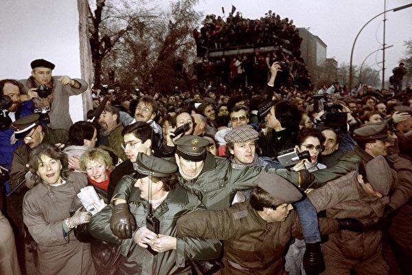 1989年11月12日,波茨坦广场的柏林墙被打开,东、西德警方控制东柏林的人潮向西德冲过去。 ( PATRICK HERTZOG/AFP/Getty Images)