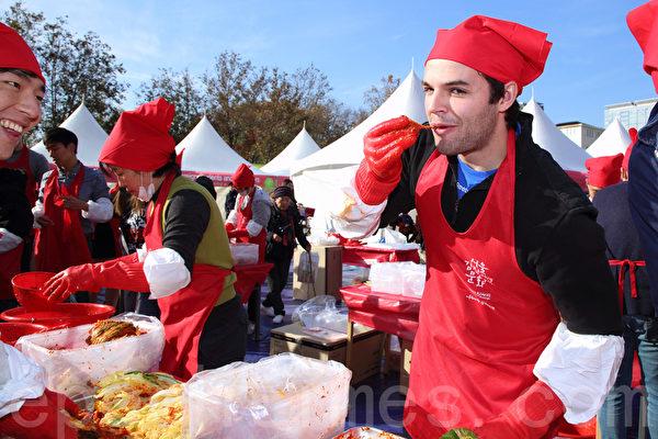 """为期3天的""""2014首尔泡菜文化节""""于11月16日落下帷幕,这也是韩国历届规模最大的泡菜庆典。图为外国人现场制作泡菜。(全宇/大纪元)"""