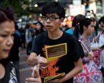 11月23日佔中團體在街站宣傳爭取真普選理念時,黃之鋒被一名男子推跌,所幸沒有受傷。圖為11月16日,香港學生領袖黃之鋒(中)手持傳單在銅鑼灣區分發給民眾。(Alex Ogle/AFP/Getty Images)