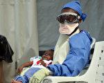 赖比瑞亚的医疗人员,正在照顾一名感染伊波拉病毒的婴孩。(AFP)