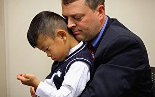 美國一名西人男子日前在社交網站上表示,他領養了一名他認定為中國人的小孩,17年後才弄清楚他是韓國人。圖為一名美國西人男子與其領養的中國男童。(Chip Somodevilla/Getty Images)