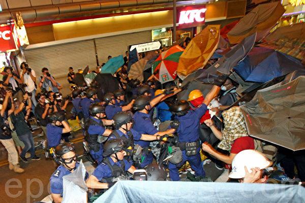 香港警方11月25日在旺角清场行动中,晚上在砵兰街朗豪坊一带首次施放催泪水剂,示威人士用雨伞抵挡,不少人被喷到,感到刺痛。警方并在场拘捕多名示威者。(潘在殊/大纪元)