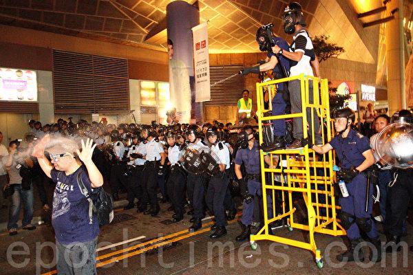 香港警方11月25日在旺角清场行动中,晚上在砵兰街朗豪坊一带首次施放催泪水剂,示威人士用雨伞抵挡,不少人被喷到,感到刺痛。警方并在场拘捕多名示威者。(蔡雯文/大纪元)