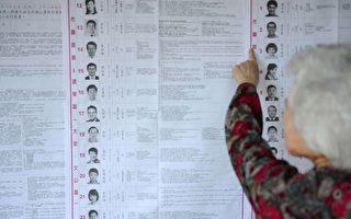 2014年11月29日台湾数以百万计的选民进行九合一选举的投票,图为一位台北民众正在检查众多的候选人名单。(SAM YEH/AFP/Getty Images)