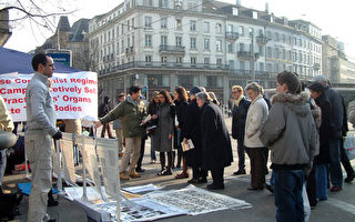 """大陆客游瑞士结队""""三退""""。图为2006年3月18日,瑞士苏黎世的法轮功学员在市中心揭露中共暴行,路人纷纷驻足观看真相展板。(大纪元)"""