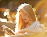快乐的金发女孩读一本书(fotolia)
